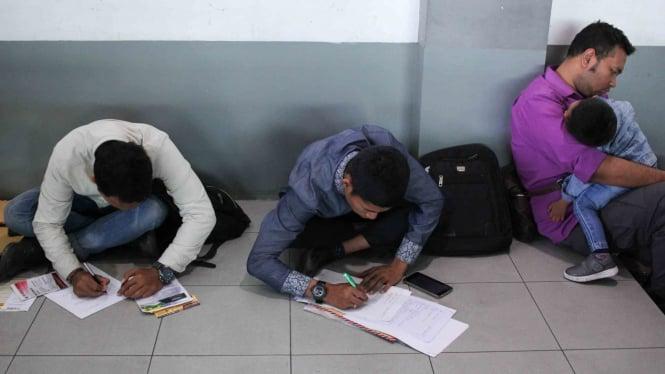 Pencari kerja menyiapkan dokumen persyaratan lamaran kerja saat bursa kerja