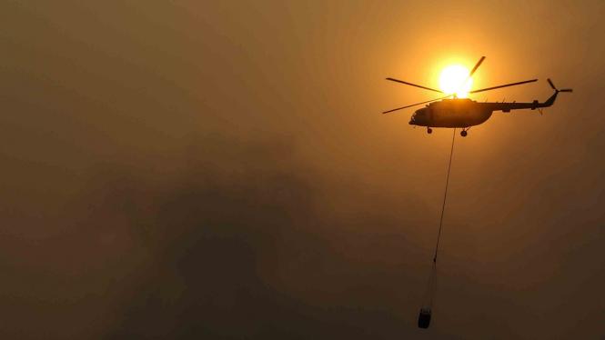 Petugas Badan Nasional Penanggulangan Bencana Nasional (BNPB) dengan Helikopter MI-18Mtv-1, melakukan pemadaman kebakaran lahan dari udara (water bombing) di Desa Rambutan, Indralaya Utara, Sumatera Selatan