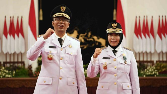 Gubernur Nusa Tenggara Barat (NTB) Zulkifliemansyah (kiri) bersama Wakil Gubernur Sitti Rohmi Djalilah mengangkat tangan seusai pelantikan di Istana Negara Jakarta