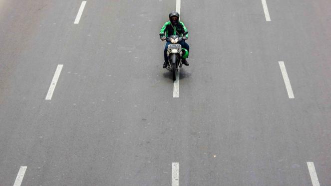 Pengendara sepeda motor melintas di jalan Sudirman, Jakarta