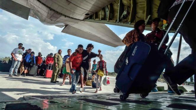 Warga terdampak gempa dan tsunami menunggu masuk ke dalam pesawat untuk dievakuasi di Palu, Sulawesi Tengah