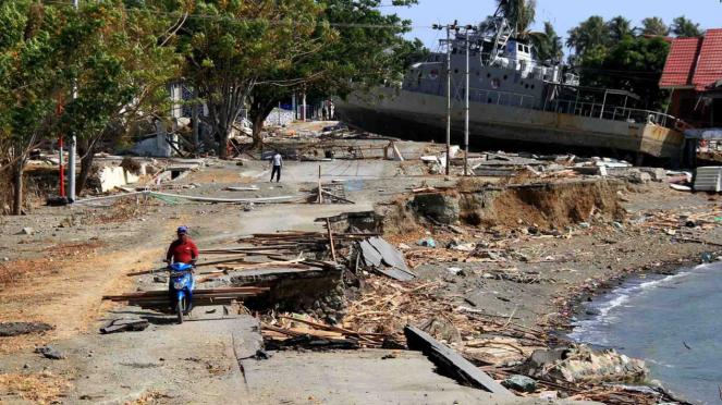 Warga berada di dekat kapal TNI AL yang terdampar di jalanan akibat tsunami di Watusampu, Ulujadi, Palu, Sulawesi Tengah, 3 Oktober 2018.