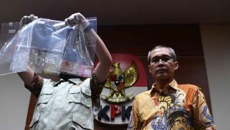 Wakil Ketua KPK Alexander Marwata (kanan) didampingi penyidik menunjukkan barang bukti hasil operasi tangkap tangan (OTT) di gedung KPK, Jakarta