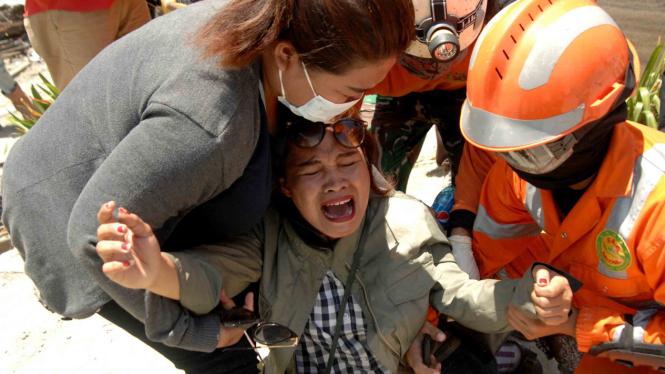 Keluarga korban menangis saat menyaksikan jenazah keluarganya dievakuasi yang menjadi korban gempa bumi dan tsunami di Hotel Mercure, Palu, Sulawesi Tengah