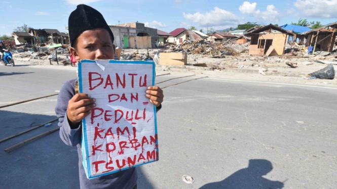 Seorang anak korban gempa dan tsunami berdiri  mengharapkan sumbangan dari pengendara yang lewat di Palu, Sulawesi Tengah