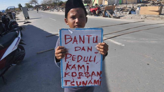 Seorang anak korban gempa dan tsunami berdiri  mengharapkan sumbangan dari penge