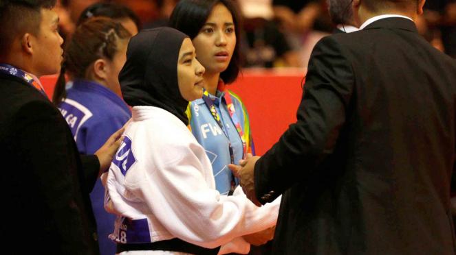 Pejudo putri Indonesia Miftahul Jannah (tengah) berunding dengan perangkat pertandingan sebelum bertanding di kelas kelas 52 kg blind judo Asian Para Games 2018 di Jiexpo Kemayoran