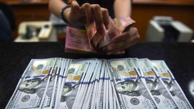 Petugas menghitung mata uang rupiah dan dolar AS di salah satu tempat penukaran uang di Jakarta