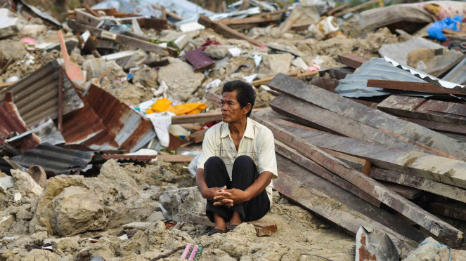 Abdullah (64), salah satu korban selamat dari bencana alam gempa dan pencairan tanah (likuifaksi) duduk disekitar puing rumahnya yang hancur dan tertimbun lumpur di Kelurahan Petobo, Palu, Sulawesi Tengah