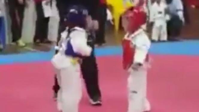 Dua bocah tanding taekwondo.