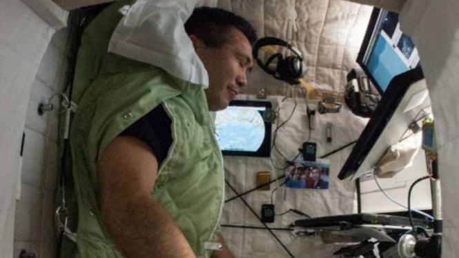 Ilustrasi astronaut NASA tidur di dalam pesawat ruang angkasa ISS.