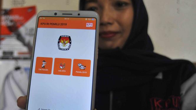Seorang warga memperlihatkan aplikasi KPU RI pada layar ponsel.