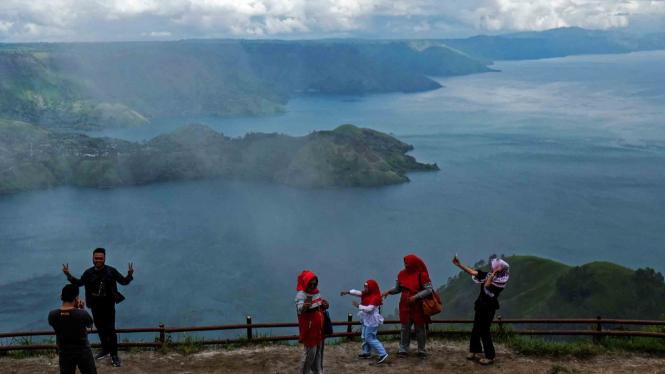 Wisatawan melihat panorama Danau Toba dari puncak