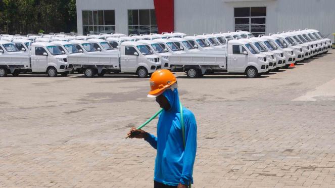Pekerja berjalan di depan deretan mobil Esemka di pabriknya di Sambi, Boyolali,