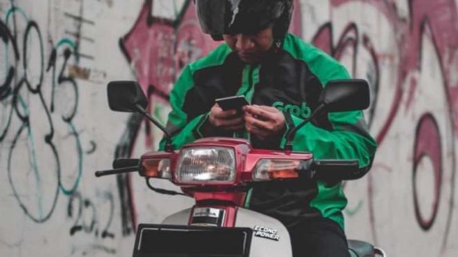Pengendara ojek online menggunakan Honda Astrea Prima