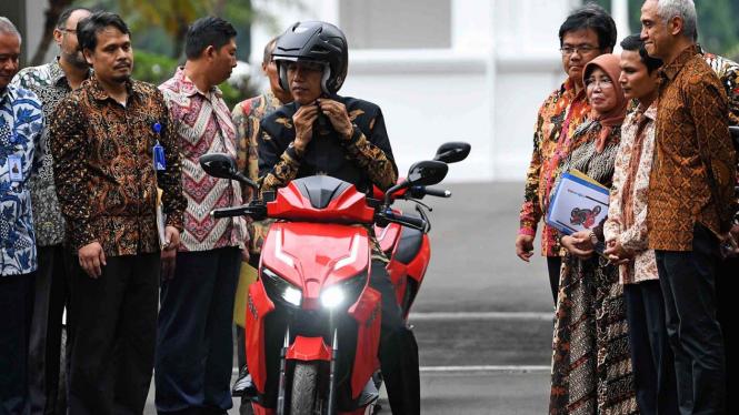 Presiden Joko Widodo mengenakan helm sebelum  menjajal motor listrik buatan dalam negeri 'Gesits' seusai melakukan audiensi dengan pihak-pihak yang terkait produksi di halaman tengah Istana Kepresidenan, Jakarta, Rabu, 7 November 2018.