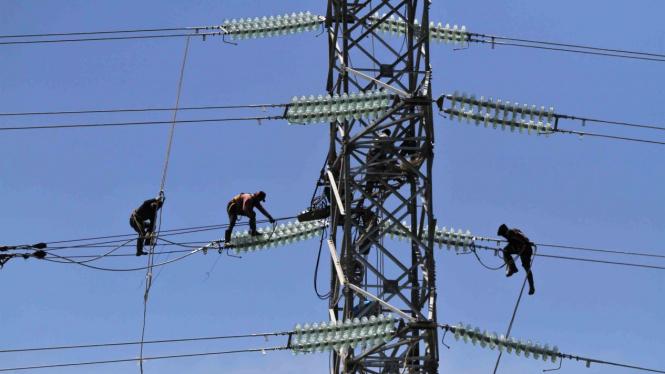 Pekerja memasang jaringan kabel ke tower milik PT PLN Persero yang akan dialiri listrik dari PLTU IPP 3 Kendari, di Desa Pousu Jaya, Konda, Konawe Selatan, Sulawesi Tenggara