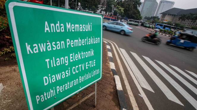 Pengendara melintas di dekat rambu tilang elektronik di Jalan Medan Merdeka Barat, Jakarta