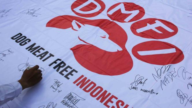 Warga membubuhkan tanda tangan pada selembar spanduk saat kampanye Indonesia Bebas Daging Anjing di Taman Apsari, Surabaya, Jawa Timur