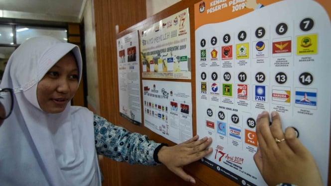 Dua siswa Sekolah Menengah Atas memperhatikan gambar partai politik peserta pemilu 2019 di Komisi Pemilihan Umum (KPU) Jawa Barat, Bandung