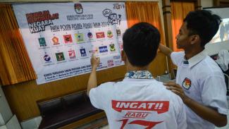Dua siswa Sekolah Menangah Atas memperhatikan gambar partai politik peserta pemilu 2019 di Komisi Pemilihan Umum (KPU) Jawa Barat, Bandung