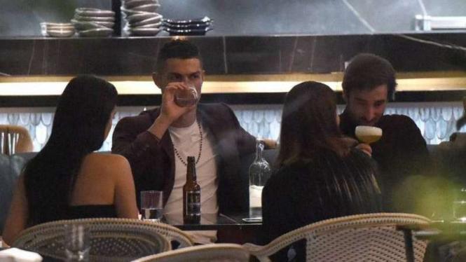 Cristiano Ronaldo sedang minum anggur di sebuah restoran di London.