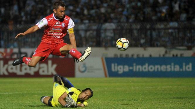 Penjaga gawang Persela Lamongan Dwi Kuswanto (bawah) berusaha menghentikan bola dari pesepak bola Arema FC Hamka Hamzah (atas) dalam lanjutan Liga 1 Indonesia di Stadion Surajaya, Lamongan, Jawa Timur