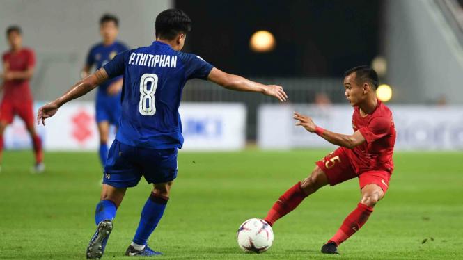 Pesepak bola Indonesia Riko Simanjuntak (kanan) berebut bola dengan pesepak bola Thailand Thitiphan Puangjan (kiri) dalam laga lanjutan Piala AFF 2018 di Stadion Nasional Rajamangala, Bangkok, Thailand
