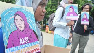 Peserta aksi menunjukkan poster dan kotak donasi pada aksi Tolak Eksekusi Baiq Nuril Maknun di Taman Kamabang Iwak Palembang