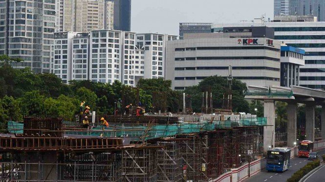 Pekerja mengerjakan proyek pembangunan jalur kereta api ringan atau light rail transit (LRT) Jabodebek koridor Cawang–Kuningan–Dukuh Atas di Jalan Rasuna Said, Kuningan, Jakarta