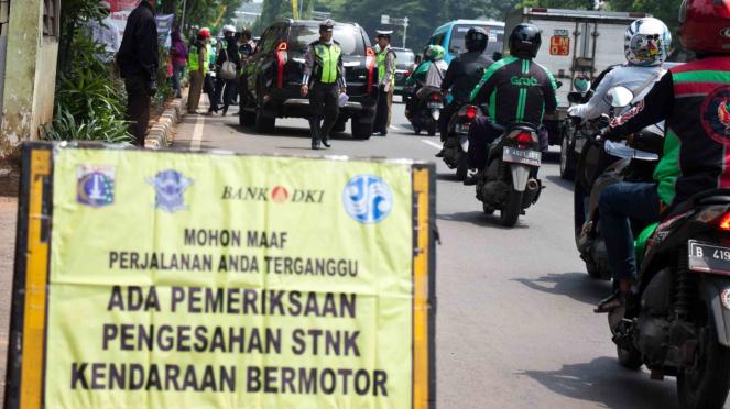 Petugas gabungan memeriksa pajak kendaraan bermotor saat razia pengesahan Surat Tanda Nomor Kendaraan (STNK) di kawasan Taman Makam Pahlawan Kalibata, Jakarta, Senin, 19 November 2018.