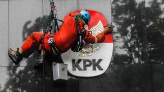 Seorang petugas sedang membersihkan logo Gedung KPK di Jakarta