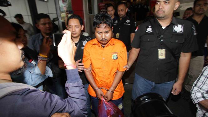 Polisi mengawal tersangka pelaku pembunuhan terhadap mantan wartawan Abdullah Fithri Setiawan alias Dufi, berinisial MN, seusai penangkapan di Polda Metro Jaya, Jakarta