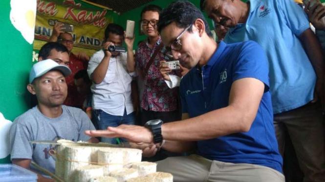 Calon wakil presiden Sandiaga Salahudin Uno belajar mengiris tempe setipis kartu ATM di sentra industri tempe Sanan, Kota Malang, Jawa Timur, pada Jumat, 23 November 2018.