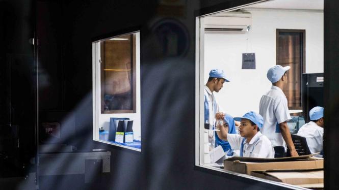 Petugas melakukan pemeriksaan visual vaksin manual sebelum pengemasan di laboratorium milik PT Bio Farma, Bandung, Jawa Barat