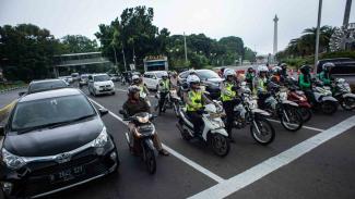 Sejumlah anggota Satlantas Polres Metro Jakarta Pusat saat melakukan sosialisasi tilang elektronik kepada masyarakat pengguna kendaraan bermotor di persimpangan Bundaran Patung Kuda, Jakarta