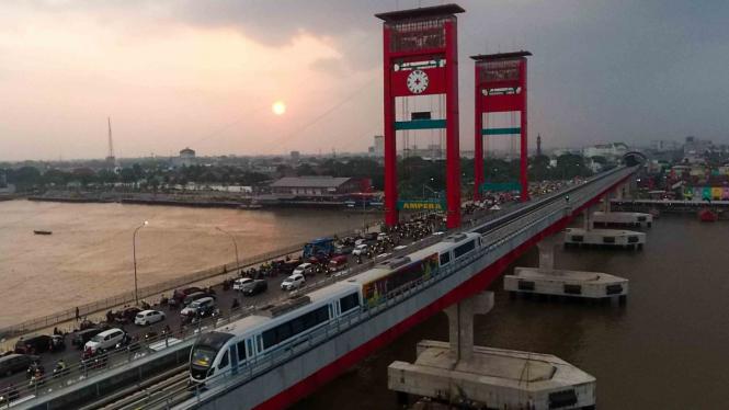 Rangkaian Light Rail Transit (LRT) Palembang melintas di atas Sungai Musi, Palembang, Sumatra Selatan.