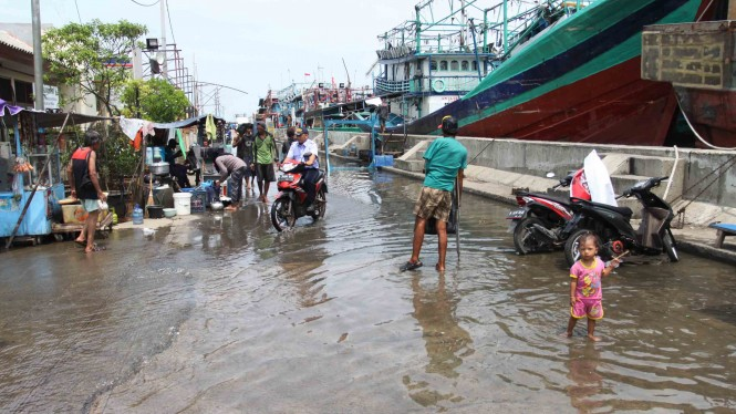 Warga melintasi genangan air banjir rob di kawasan akses pintu masuk menuju pelabuhan Muara Angke, Jakarta Utara