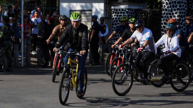 Presiden Joko Widodo (kiri) didampingi Menteri BUMN Rini Soemarno (kanan) dan Dirut BTN Maryono (kedua kanan) bersepeda menuju lokasi penyambungan instalasi listrik PLN gratis melalui sinergi BUMN untuk masyarakat di Bogor, Jawa Barat, Minggu, 2 Desember
