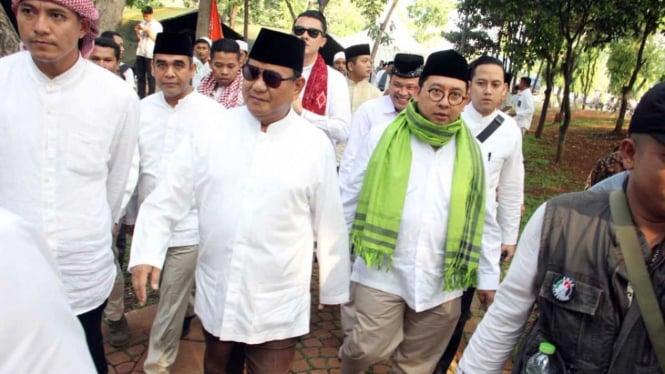 Calon presiden nomor urut 02, Prabowo Subianto (tengah) dan Fadli Zon (kedua kanan) jalan kaki ke lokasi Reuni 212 di Monas Jakarta.