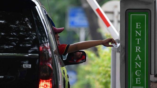Pengendara mobil mengambil karcis parkir di lapangan IRTI Monas, Jakarta Pusat, Jakarta