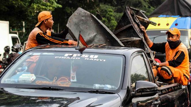 Petugas kebersihan mengangkut barang sisa perusakan dan pembakaran di Polsek Ciracas, Jakarta, Rabu, 12 Desember 2018.