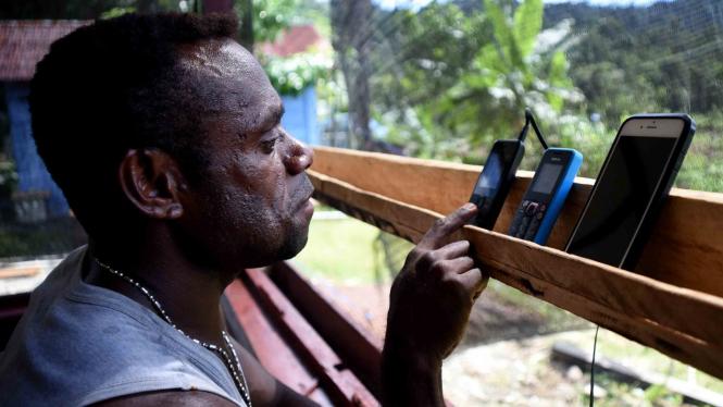 Seorang warga menggunakan telepon genggamnya di pelosok Mosairo, Nabire, Papua