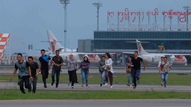 Penumpang berlari menyelamatkan diri saat simulasi penanganan kecelakaan pesawat, di Bandara I Gusti Ngurah Rai, Bali