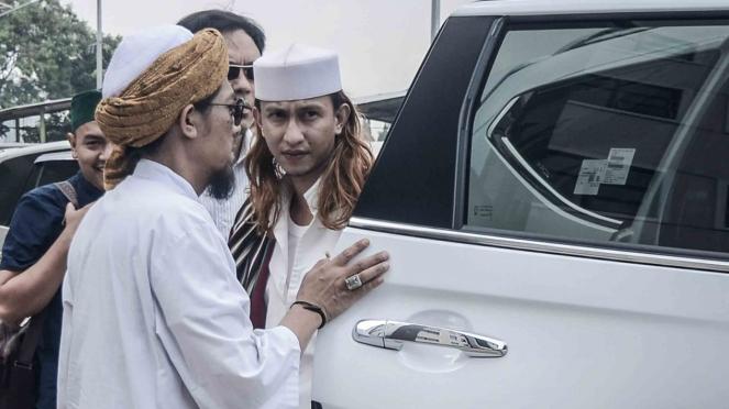 Habib Bahar bin Ali bin Smith (kanan) keluar dari kendaraannya untuk menjalani pemeriksaan perdana di Direktorat Kriminal Umum Polda Jawa Barat, Bandung, Jawa Barat, Selasa, 18 Desember 2018.