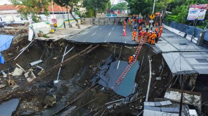 Sejumlah petugas pemadam kebakaran memeriksa kondisi tanah ambles di Jalan Raya Gubeng, Surabaya, Jawa Timur, Rabu, 19 Desember 2018.