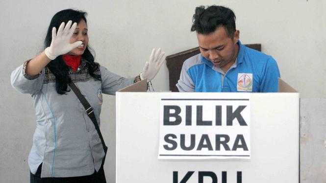 Petugas KPPS membantu seorang penyandang disabilitas Orang Dengan Gangguan Jiwa (ODGJ) membuka surat suara di bilik suara saat simulasi pemilu bagi ODGJ di Kota Blitar, Jawa Timur