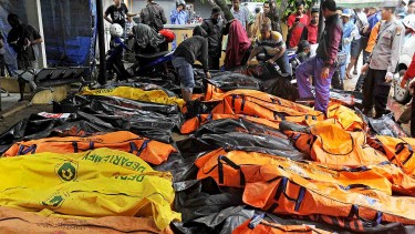 Sejumlah relawan mengumpulkan jasad korban meninggal dunia akibat gelombang tsunami untuk dievakuasi ke rumah sakit di Pantai Sembolo, Carita, Pandeglang, Banten, ke Puskesmas Labuhan