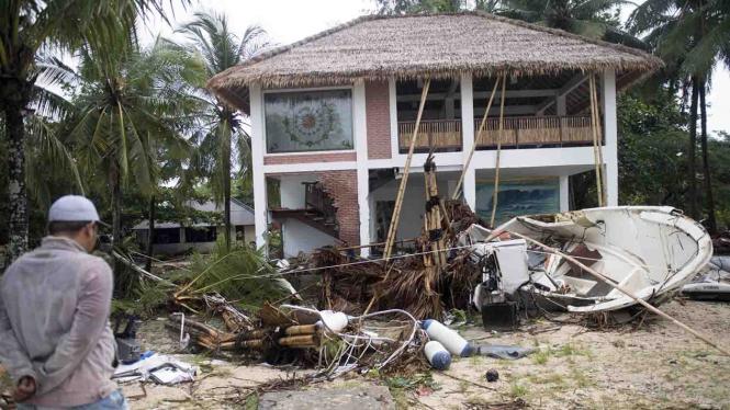 Warga berada di depan bangunan yang terdampak bencana Tsunami di Pantai Tanjung Lesung, Banten, Jawa Barat, Minggu, 23 Desember 2018.