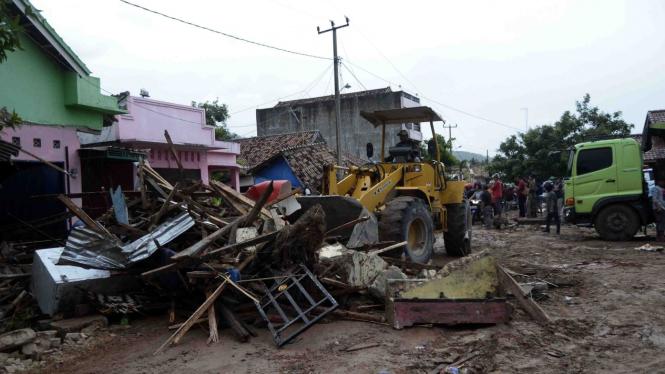 Petugas dengan menggunakan alat berat membersihkan sisa-sisa bangunan yang tersapu tsunami di jalan Desa Way Muli, Kecamatan Rajabasa, Lampung Selatan, Lampung